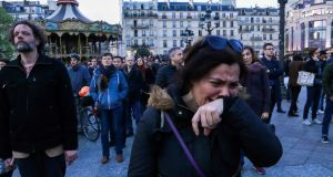 A woman cries as people look at Notre Dame  engulfed in flames from the Paris's Hotel de Ville esplanade on Monday. Photograph: STR/AFP/Getty Images