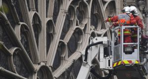 Firefighters assess  damage to  Notre Dame Cathedral in Paris after the massive fire on Monday. Photograph: Victoria Jones/PA Wire