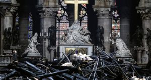 Notre Dame altar surrounded by charred debris: the outpouring of emotion points to Notre Dame having an importance which is cultural and not just religious.  Photograph: Ludovic Marin