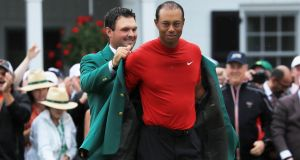Tiger Woods is assisted by previous winner Patrick Reed as he dons the green jacket following his victory at the US Masters at Augusta National. Photograph:  David Cannon/Getty Images