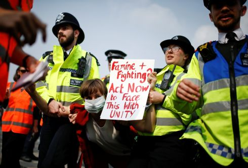 Police officers detain a climate-change activist at Waterloo Bridge during the Extinction Rebellion protest in London. Photograph: Henry Nicholls
