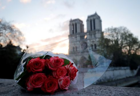 A bunch of roses placed near Notre Dame Cathedral at sunrise. Photograph: Philippe Wojazer/Reuters