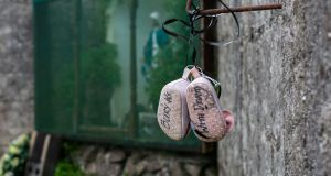 A pair of baby shoes with the message 'Bury us with dignity' hangs on a wall at the site of the Tuam mother-and-baby home. Photograph: Andy Newman