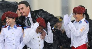 Brazilian president Jair Bolsonaro and  of military college students during a downpour as they attend a ceremony to mark Army Day, in Brasilia on Wednesday. Photograph: Sergio Lima/AFP/Getty Images