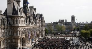 Hundreds of people gather in front of the Paris city hall in France during a tribute to the Paris firefighters who saved Notre Dame Cathedral from collapse. Photograph: EPA