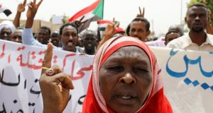 Protesters wave Sudanese flags, hold banners and chant slogans during a demonstration in front of the defence ministry in Khartoum, Sudan. Photograph: Umit Bektas/Reuters