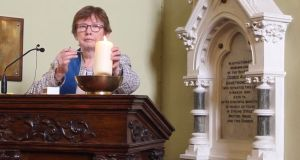 Rev Bridget Spain lights a candle in honour of Lyra McKee at the Unitarian Church's Good Friday service for the victims of the Troubles. Photograph: Ronan McGreevy