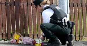 A police officer lays flowers passed to her by members of the public at the scene where journalist Lyra McKee was fatally shot in Derry. Photograph: Paul Faith/AFP/Getty Images