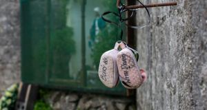 A pair of baby's shoes with the words 'Bury us with Dignity' hanging on a wall at the site of the Tuam Mother-and-Baby Home. Photograph: Andy Newman