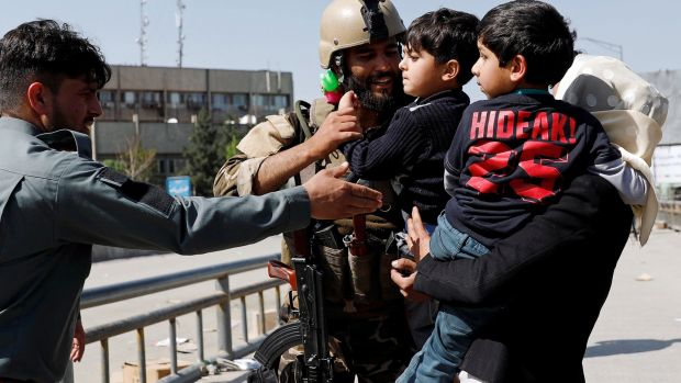 An Afghan security force officer carries a child rescued from the building of ministry of communication and information technology in Kabul. Photograph: Mohammad Ismail/Reuters