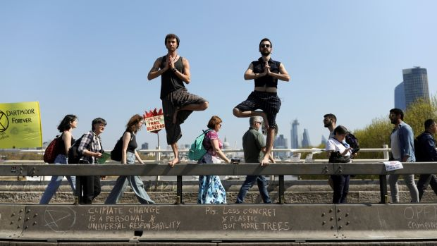 Climate change activists practise yoga on Waterloo Bridge in London. Photograph: Simon Dawson/Reuters