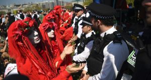 Protesters and police during  Extinction Rebellion climate change protests on Waterloo Bridge in London. Photograph: Neil Hall/EPA