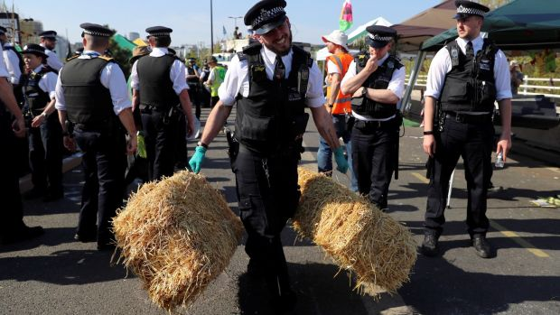 A police officer removes haystacks during the Extinction Rebellion protest on Waterloo Bridge in London. Photograph: Simon Dawson/Reuters