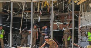 A Sri Lankan Police officer inspects a blast spot at the Shangri-la hotel in Colombo on Sunday. Anita Nicholson and her children Alex (14) and Annabel (11) were having breakfast when the suicide bomb attack occured.  Photograph: Chamila Karunarathne/AP