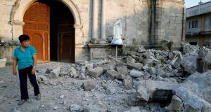 A resident looks at the rubble of St Catherine church, including a toppled head of a statue, following an earthquake in Porac township, Pampanga province, north of Manila. Photograph: Bullit Marquez/AP