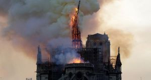 The steeple of Notre-Dame cathedral collapses as the cathedral is engulfed in flames. Photograph: Geoffroy van der Hasselt/AFP/Getty Images