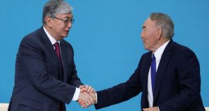 Kazakhstan's interim president Kassym-Jomart Tokayev shakes hands with former president Nursultan Nazarbayev: snap presidential election is due in June. Photograph: Mukhtar Kholdorbekov