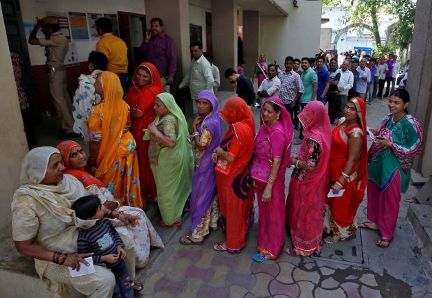 People wait in queues to casts their votes at a polling station on Tuesday. Photograph: Amit Dave/Reuters