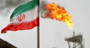 A gas flare on an oil production platform beside a national flag in Iran: exports have fallen to a million barrels per day. Photograph: Raheb Homavandi