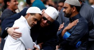 People comfort each other before the Friday prayers at Hagley Park outside Al-Noor mosque in Christchurch, New Zealand. File Photograph: Edgar Su/Reuters