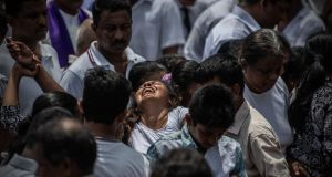 SRI LANKA BOMBINGS: A woman cries as a coffin is buried during a mass burial near St Sebastian's Church in Negombo, Sri Lanka. Photograph: Carl Court/Getty Images