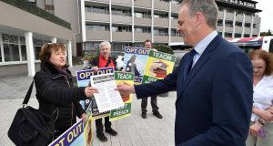 Jane Donnelly of Atheist Ireland hands Minister for Education Joe McHugh her protest at the TUI conference in Killarney on Wednesday. Photograph: Don MacMonagle