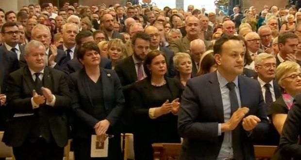 Arlene Foster, Mary Lou McDonald and others applaud during Fr Magill's homily