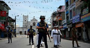 Priests walk on a blocked street as soldiers stand guard outside St Anthony's Shrine in Colombo on Thursday. Photograph: Jewel Samad/AFP/Getty Images