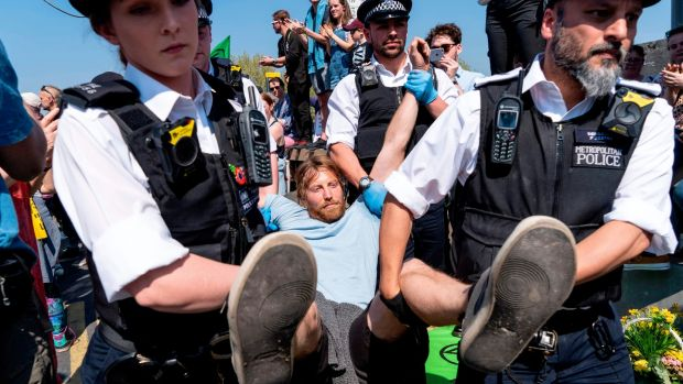 Police officers arrest and carry away a climate change activist from Waterloo Bridge on April 21st. Photograph: Niklas Halle'n / AFP
