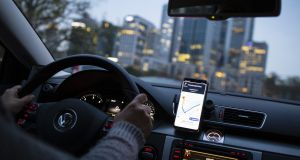 A dashboard-mounted smartphone displays the Uber Technologies  app as an Uber X driver heads towards skyscrapers in the 'Mainhattan' financial district in Frankfurt, Germany.  Photographer: Alex Kraus/Bloomberg