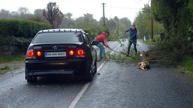 Quick thinking motorists clear the roadway after a fallen tree blocked the main Killarney to Dingle road at Aghadoe, Killarney during the height of Storm Hannah on Friday evening. Photograph: Don MacMonagle