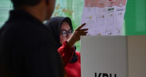 A woman looks at her ballot during a revote due to logistical issues in Indonesia's general election in Banda Aceh. Photograph: Chaideer Mahyuddin/AFP/Getty Images