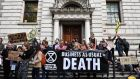 Climate change activists stage a protest outside the HM Treasury building in central London, during environmental protests by the Extinction Rebellion group. Photograph: Daniel Leal-Olivas/AFP