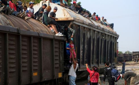 MIGRANT TRAIN: Central American migrants climb onboard a train known as The Beast, continuing their journey towards the United States, in Ixtepec, Mexico. Photograph: Jose de Jesus Cortes/Reuters