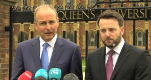 Micheál Martin and Colum Eastwood speaking outside Queen's University Belfast. Photograph: Michael McHugh/PA
