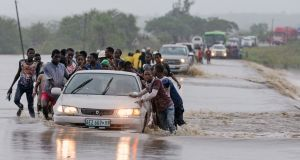 People push a car on a flooded road in Metuge, Cabo Delgado, northern Mozambique on Sunday after the area was hit by Cyclone Kenneth. Photograph: Antonio Silva/EPA