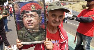 A supporter of Venezuelan president Nicolas Maduro displays a picture of late leader Hugo Chavez during a rally on May Day in Caracas. Photograph: Juan Barreto/AFP/Getty Images