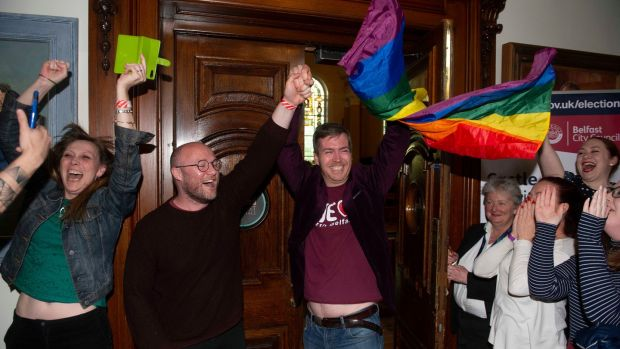 Michael McCartan celebrates with his partner Malachi O'Hara (centre) of the Green Party at Belfast City Hall. Photograph: Mark Marlow/PA Wire