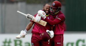 John Campbell celebrates his century with fellow West Indies opener  Shai Hope during the Tri Series One-Day International against Ireland at castle Avenue in Clontarf. Photograph: Oisín Keniry/Inpho
