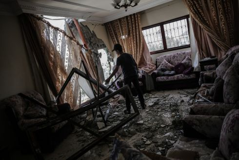 TUMBLING DOWN: A Palestinian inspects his damaged home, hit during Israeli air strikes on Gaza City, amid an escalation in violence in the region over the weekend. At least 25 Palestinians and four Israelis died. Photograph: Mohammed Saber/EPA