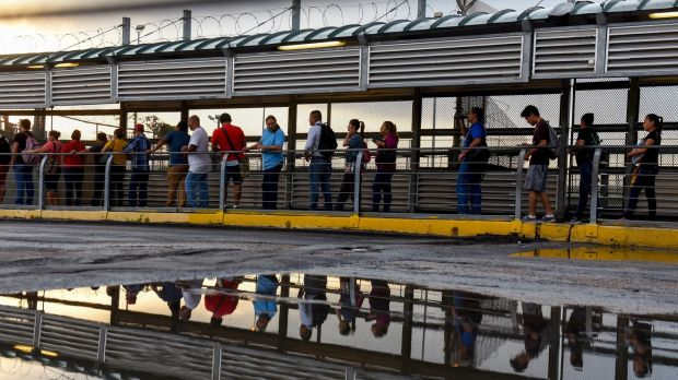 Dozens of people entering the US from Reynosa, Mexico, on the US side of the McAllen-Hidalgo International Bridge in Hildago, Texas. Photograph: Callaghan O'Hare/The New York Times
