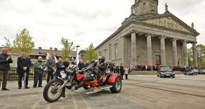 The hearse carrying the remains of Eugene McGee, led out by his daughter Linda on the trike he purchased for her, leaves St Mel's Cathedral in Longford following his funeral mass on Thursday afternoon as the members of his 1982 winning team form a guard of honour. Photograph: Lorraine Teevan