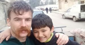 "Morgan Mansfield in the city of Afrin, Syria with a local child. He saw ""terrible things"" during his time in the war-torn country, including a family bombed while trying to flee."