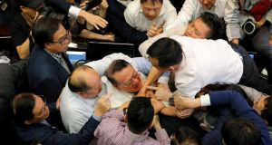 Pro-democracy and pro-Beijing lawmakers scuffle in the chamber at legislative council in Hong Kong on Saturday. Photograph: Kin Cheung/AP