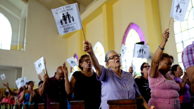 "Worshippers wave paper flags that read in Spanish ""I am in favour of the original design. The family as God created it. Wedding between man and woman"", during a service at a Methodist Church in Havana, Cuba, in October 2018. File photograph: Alexandre Meneghini/Reuters"
