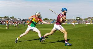 Galway's Johnny Coen clears away from Paul Doyle of Carlow. Photograph: Tommy Grealy/Inpho