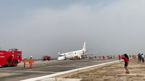 An evacuated passenger records firefighters attending the scene after a Myanmar National Airlines flight UB103 landed without a front wheel at Mandalay International Airport in Tada-U. Photograph: Reuters