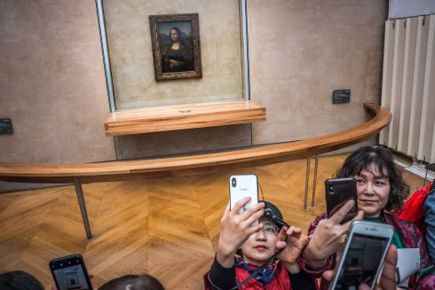 Visitors take photographs of Leonardo da Vinci's painting La Gioconda (Mona Lisa) at the Louvre Museum in Paris. The painting is a portrait of Lisa Gherardini, the wife of Francesco del Giocondo, and is in oil on a white Lombardy poplar panel. It's believed it has been painted between 1503 and 1506.  Photograph: Christophe Petit Tesson/EPA