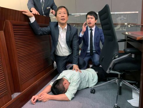 Pro-democracy politician Gary Fan lies down after clashs with pro-Beijing politicians during a meeting for control of a meeting room to consider the controversial extradition Bill, in Hong Kong, China. Photograph: James Pomfret/Reuters