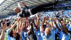 Manchester City players throw manager Josep Guardiola in the air as they celebrate winning the Premier League title. Photograph:  Mike Hewitt/Getty